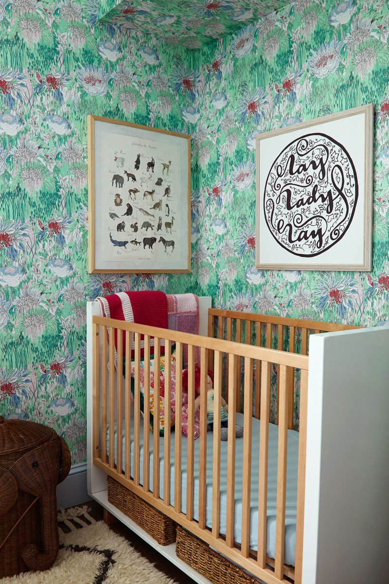 Blue trim grounds the floral Tres Tintas wallpaper—purchased at Studio Four—in the nursery.