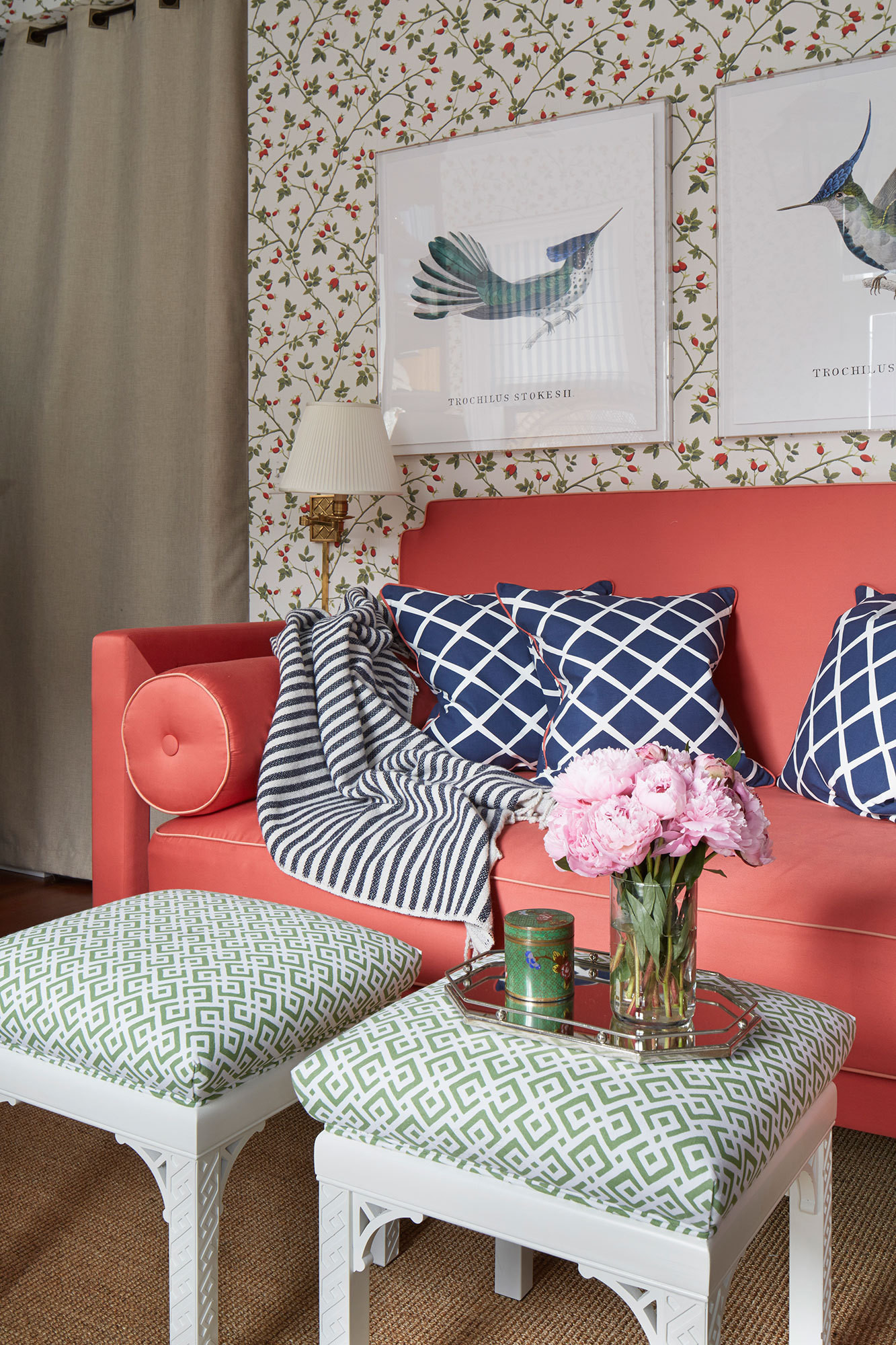 A coral-hued daybed topped with throw pillows by Serena & Lily is backed by Stark's Kerstin wall covering.