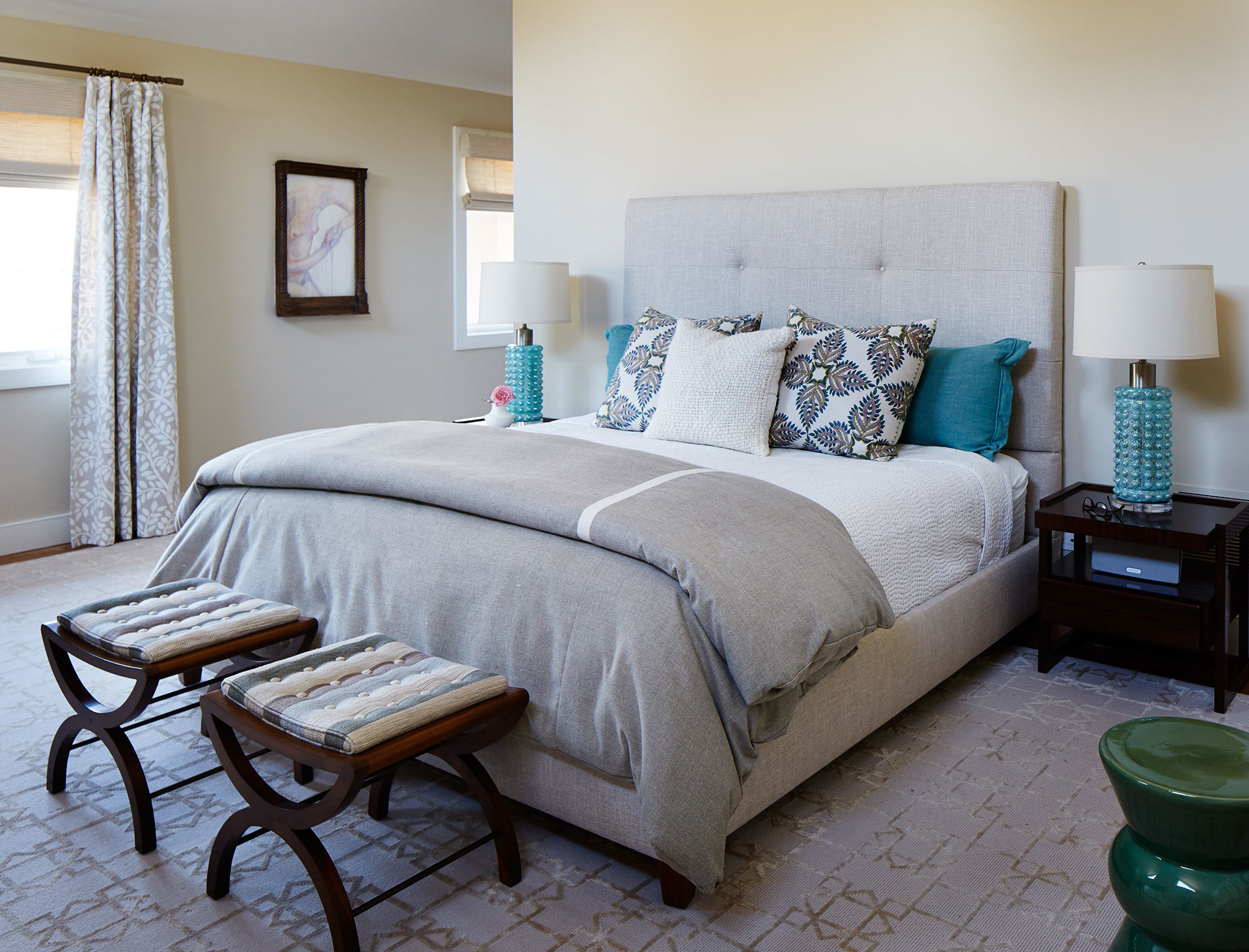 In the master bedroom, Dunbar stools outfitted with striped cushions, printed pillows by John Robshaw, and a pair of turquoise lamps combine for the home's beachiest moment.