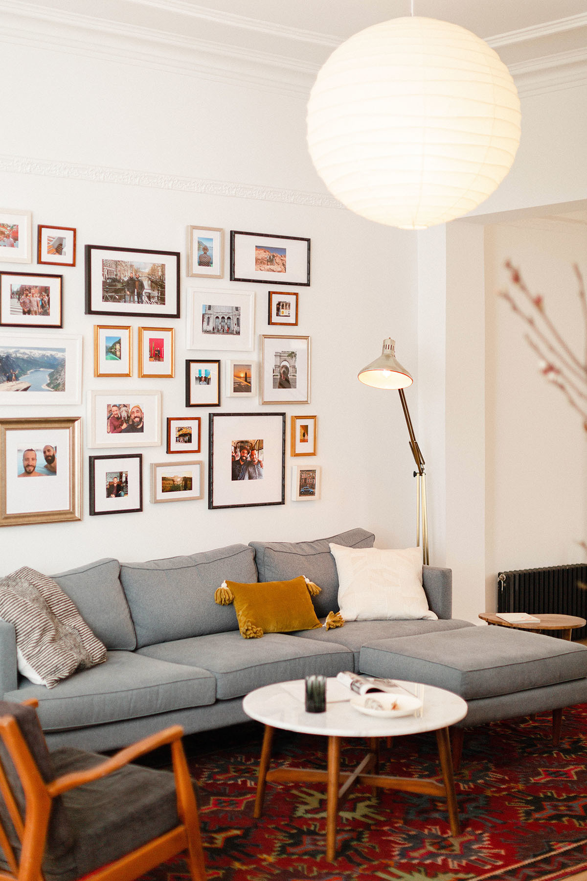 A Framebridge gallery wall brings personality to the duo's reimagined living space. Sherwin-Williams Paint | Joybird Sofa | Vintage Rug | eBay Vintage Floor Lamp | Etsy Vintage Armchair | Hayneedle Coffee Table | eBay Vintage Lamp | Urban Outfitters Accent Table | Noguchi Pendant Light.