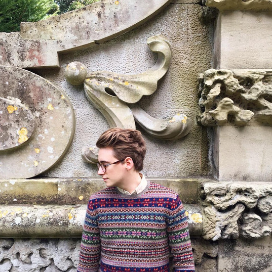 In signature spectacles and jumper in Fonthill Bishop, Wiltshire, UK.
