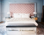 Bedroom - A tufted headboard with a pair of mirrored bedside tables