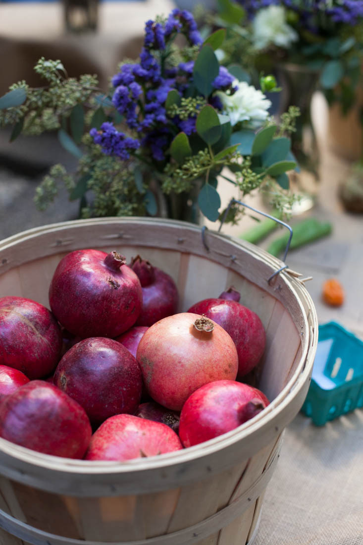 A bushel of pomegranates takes pride of place atop a vendor's table.