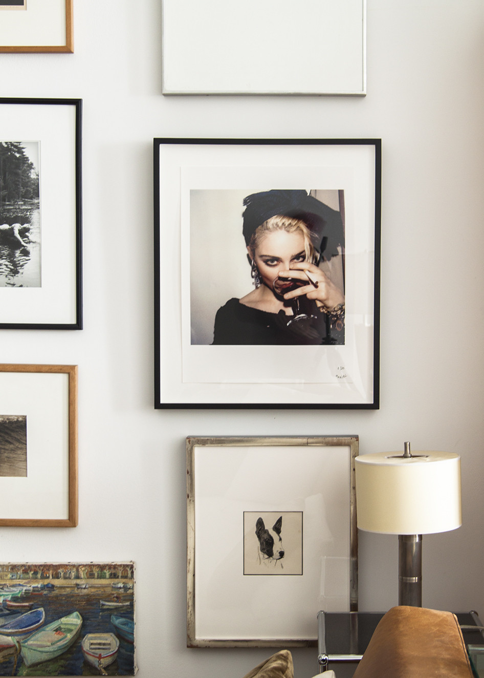 A gallery wall of portraits, paintings, and favorite photographs hangs on one wall in the living room.