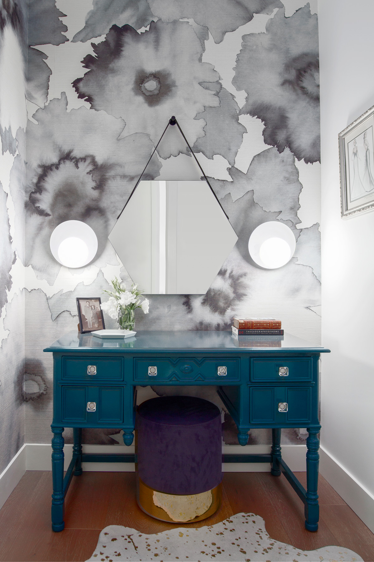 Phillip Jeffrieswallpaper gives a floral pop to the powder room while two coolCedar & Moss sconces add a modern edge. A stool from AllModern provides a glam finish.