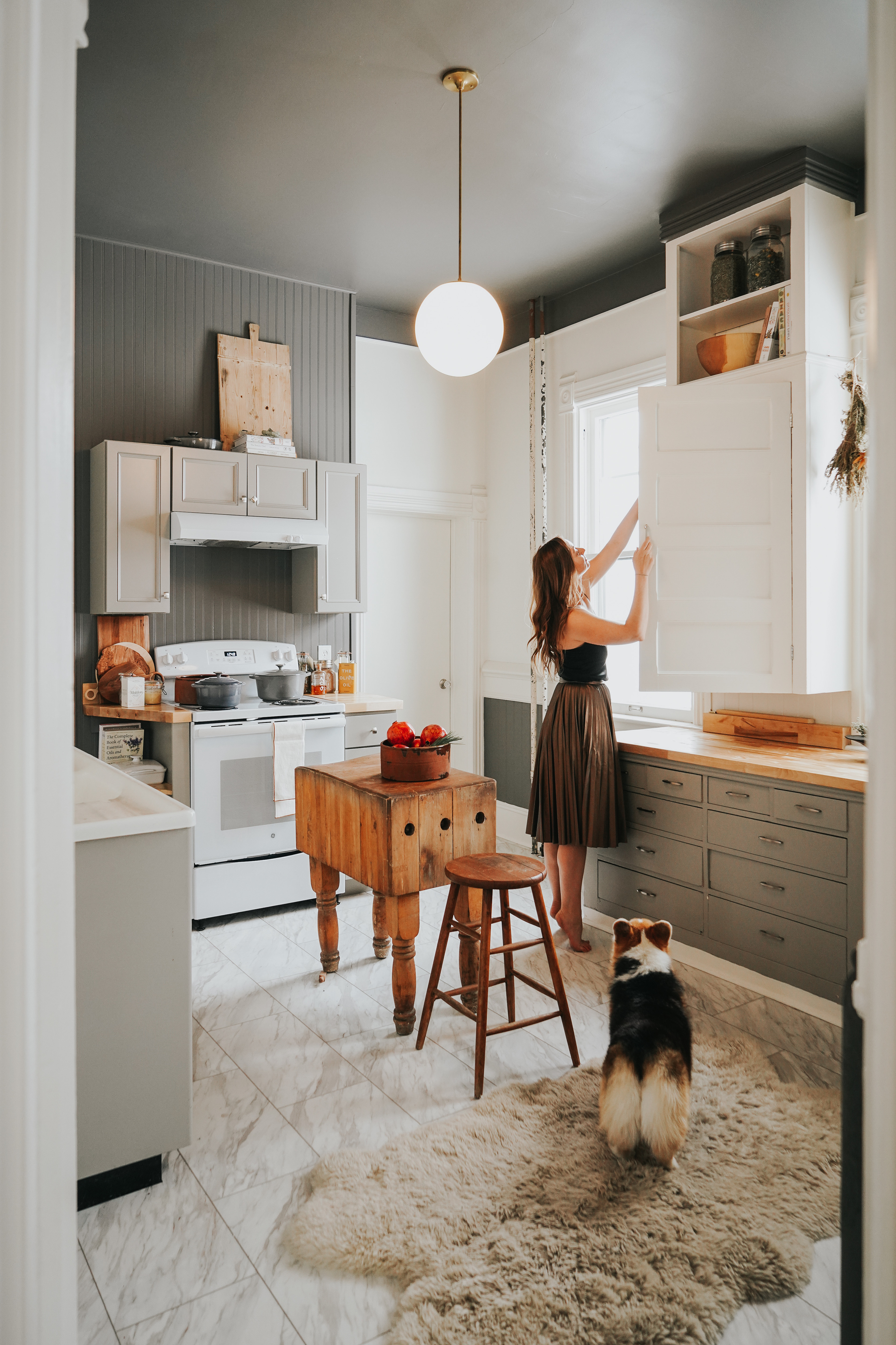 Modern fuses with tradition for a fresh take in the kitchen. Schoolhouse Electric Pendant Light; Antique Butchers Block Table; Elsie Green Vintage Bread Board; Overstock Sheepskin Rug; Vintage Stool.