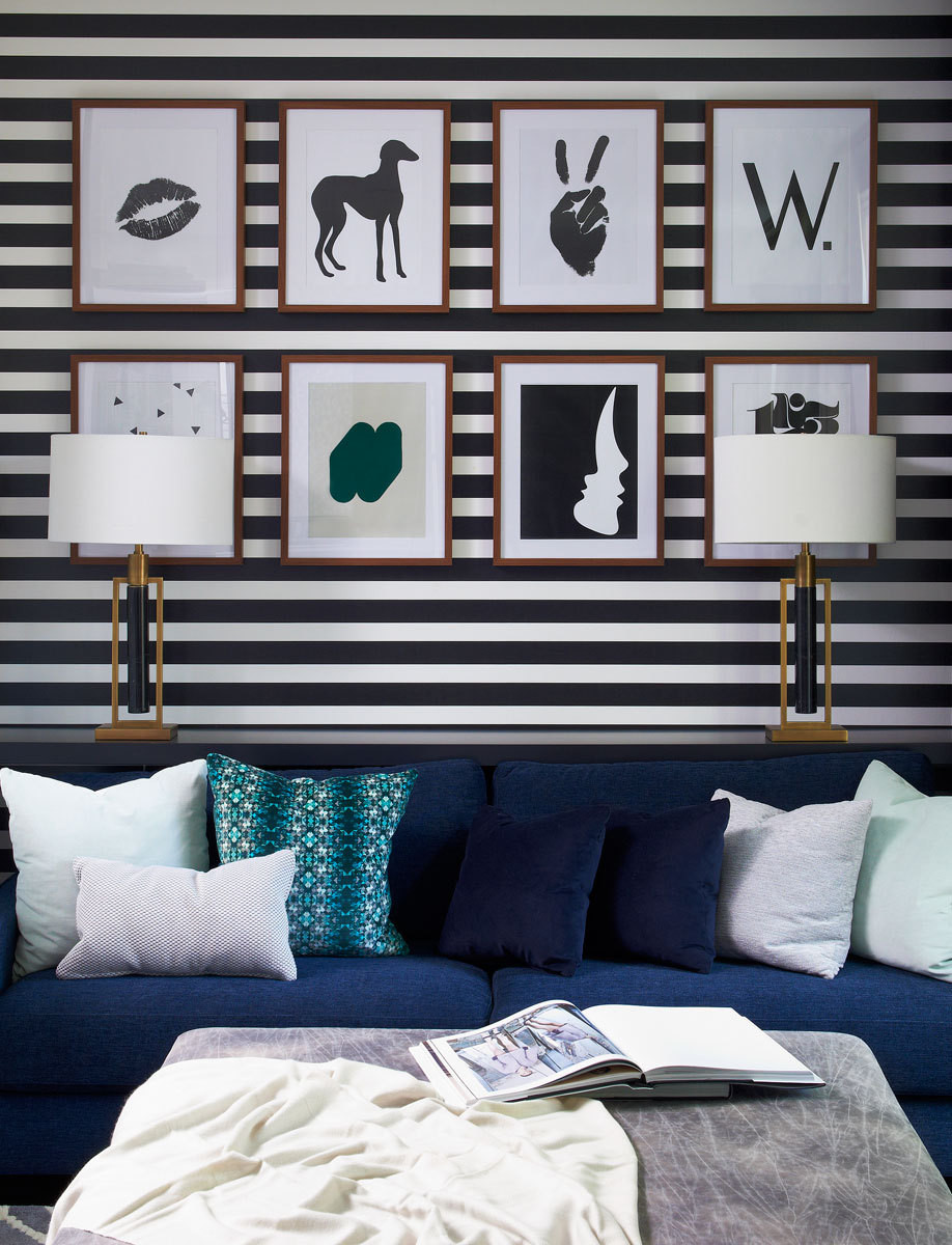 Horizontal-striped wallpaper adds depth and dimension when paired with a velvet sofa in the den.