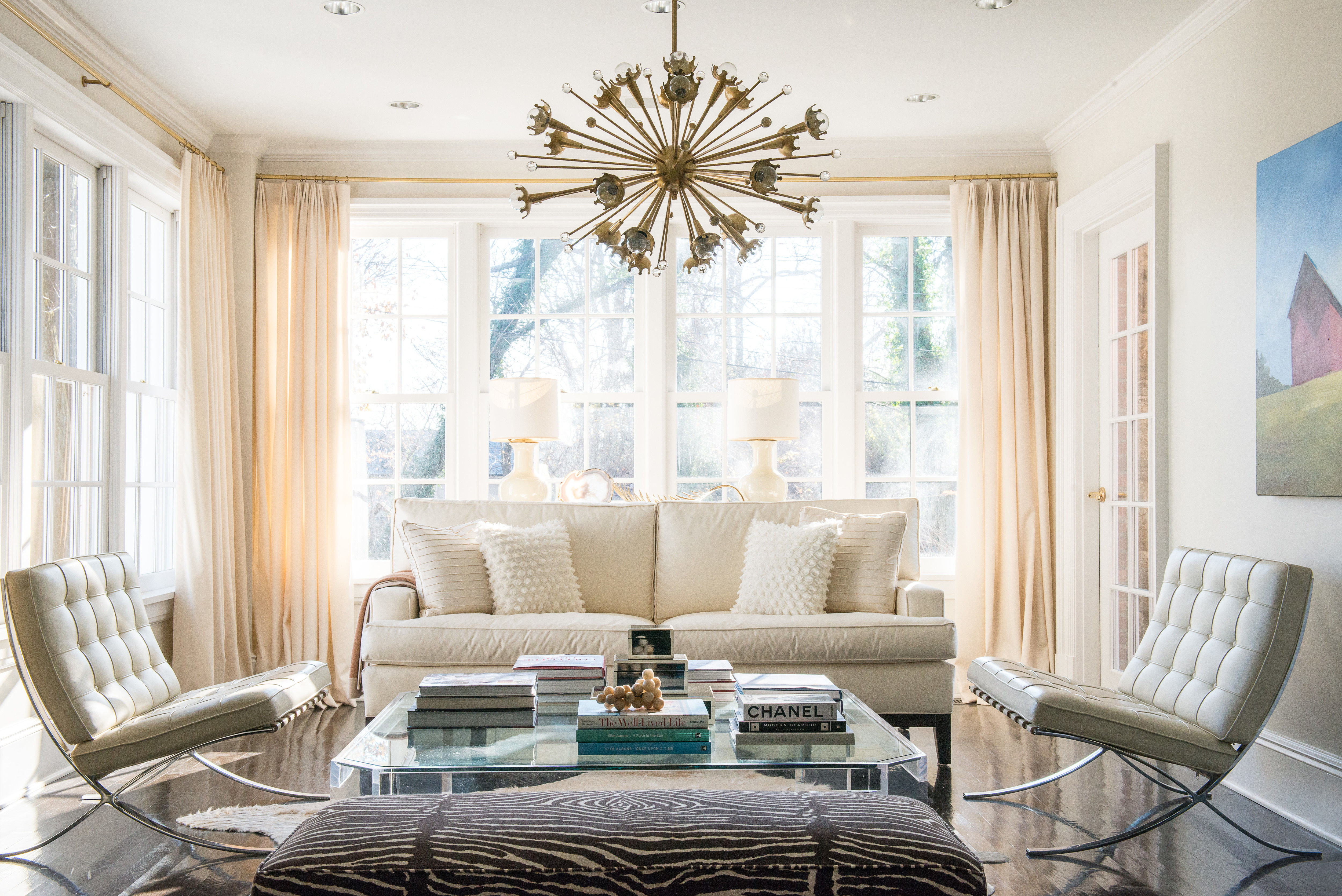 The spacious seating area is inviting and is anchored with a hide rug, lucite coffee table, and stacked art books.
