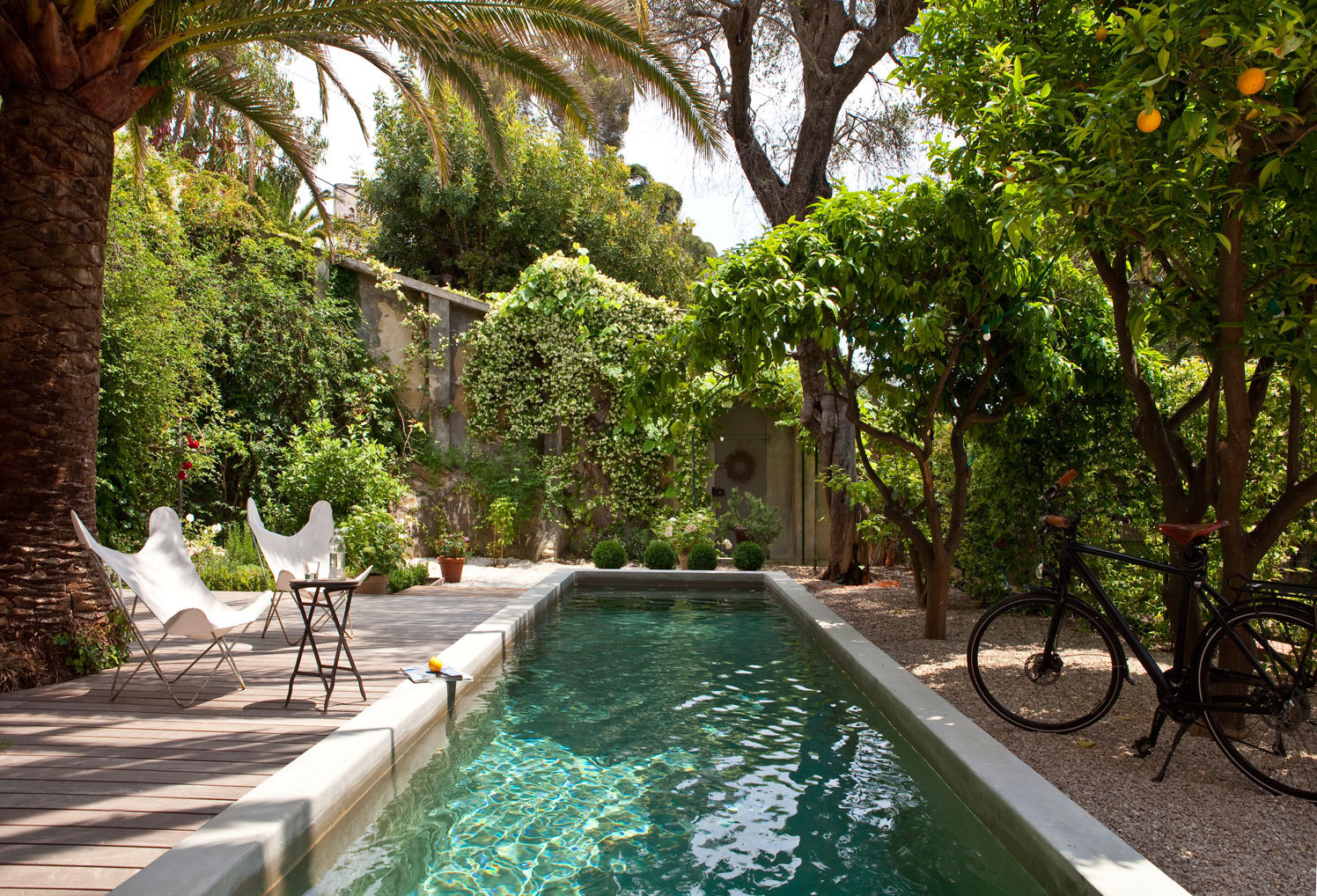 Butterfly chairs flank a minimalist swimming lane in the garden of a home in Nice, designed by Italian architect Piercarlo Dondona.