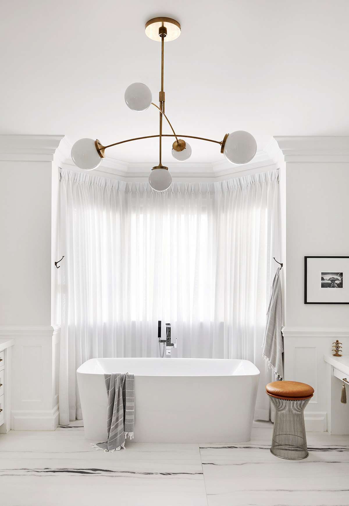 Bing finds respite from a long workday in this dreamy marble bathroom with freestanding tub.Lou & FriendsHammam Towels |Platner Stool|Visual Comfort Kate Spade Prescott 5-Light Chandelier.