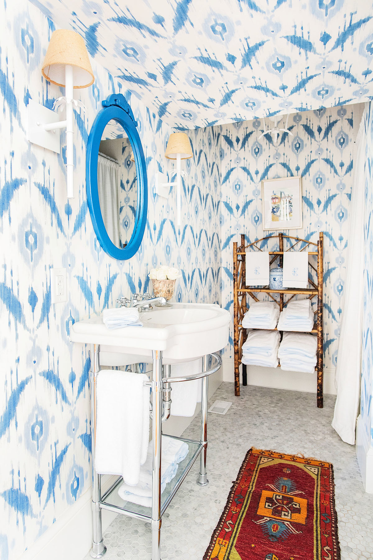 """This little powder room is tucked away and almost hidden beneath our stairs, so I love that when someone opens the door it's this unexpected pop of color,"" says Eichholz. Thibaut Wallpaper 
