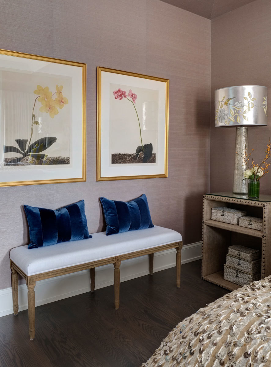 One corner of the space spotlights a sparkling table lamp by Jamie Young and a pair of classic botanical prints.