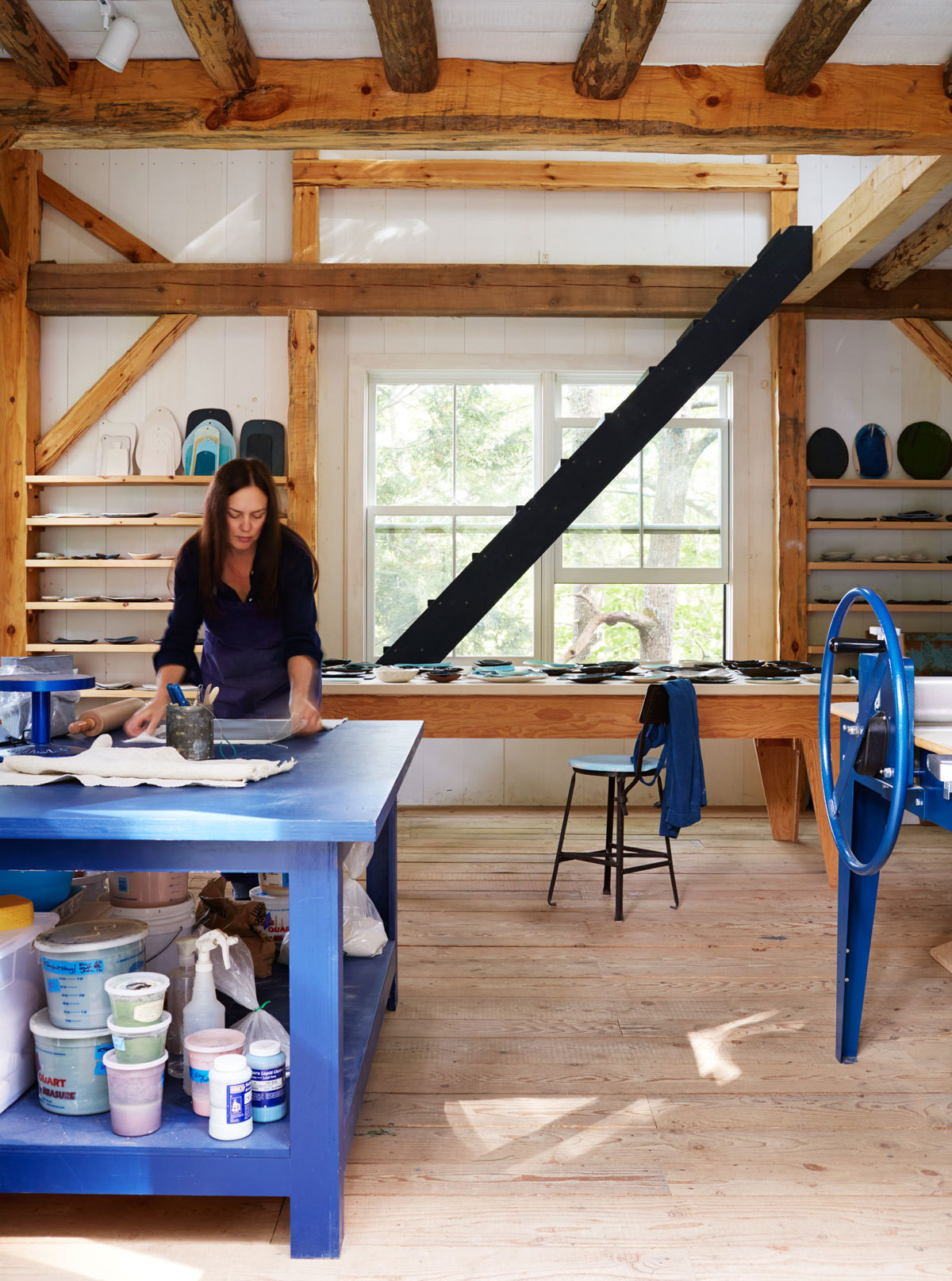 Michael at work in her barn studio, with her cobalt-blue North Star slab roller to her left and pieces from her collection lining the shelves and table behind her.