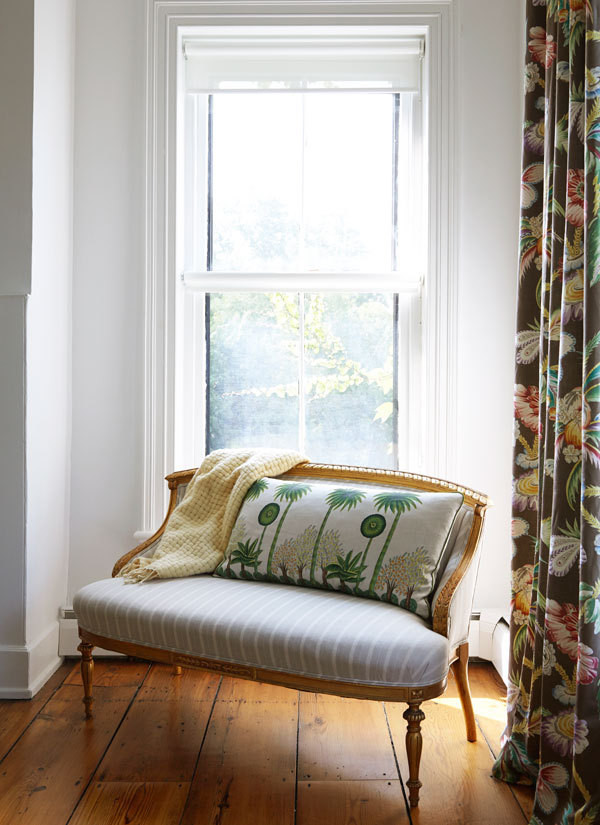 Verdant prints dress the window and love seat of a guest bedroom.