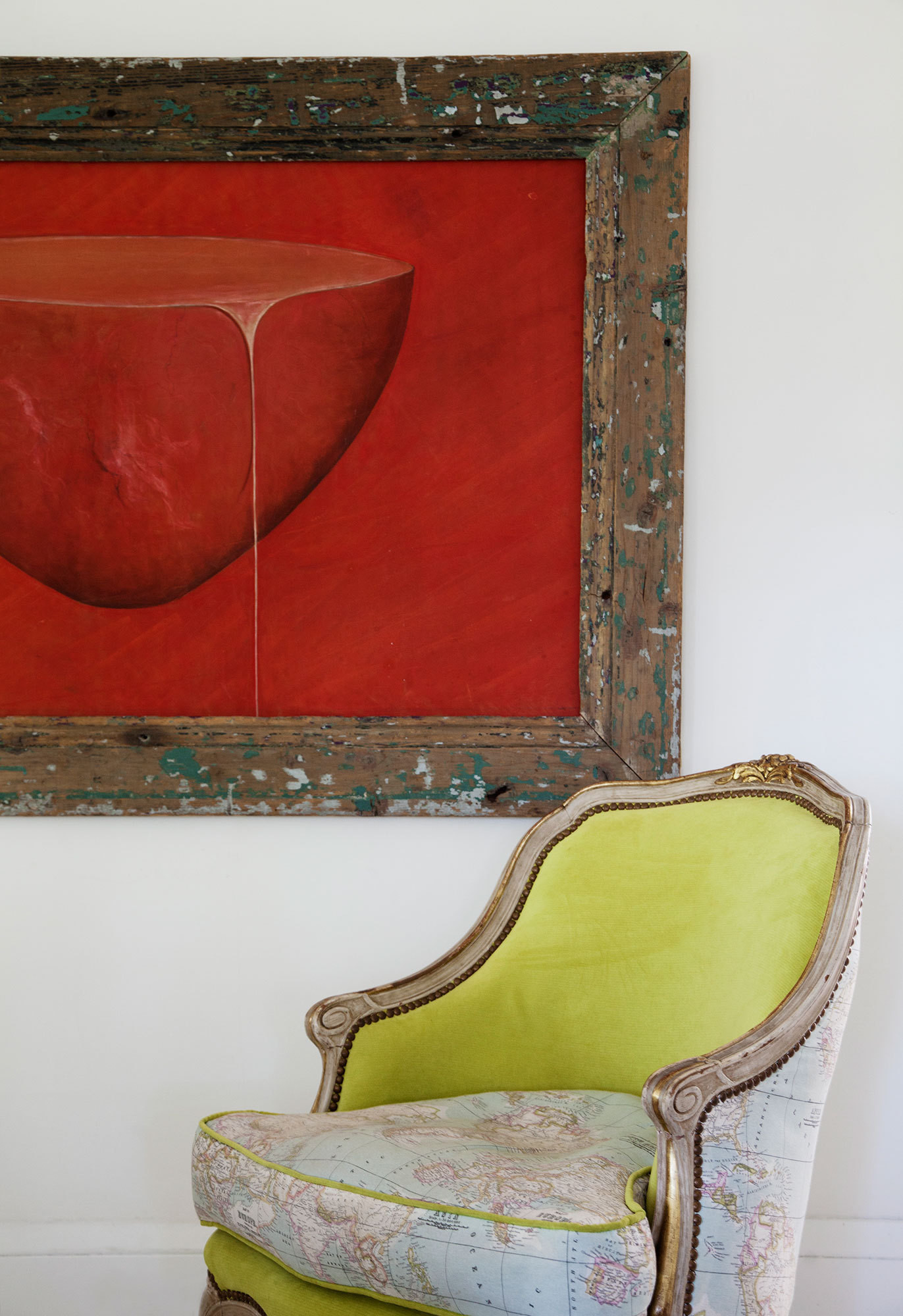 An antique chair reupholstered in map-printed fabric and acid-green velvet looks even more compelling next to a deep-red painting.