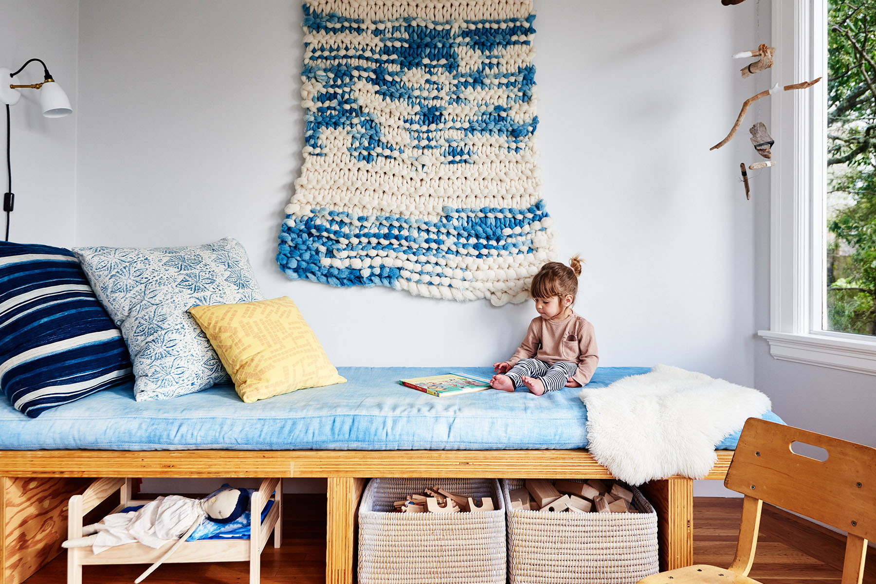 Martinez' home is filled with childlike treasures, including this striking custom-made wall hanging, created for the designer by her close friend Lana Weber of de Lana Textiles. Custom Daybed | de Lana Textiles Bedding | The Container Store Baskets | Custom, Jenny Pennywood Pillows | Amazon Sheepskin | Custom Branch Mobile | Barn Light Electric Wall Sconce.