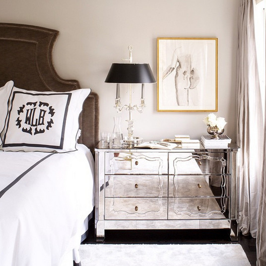 A mirrored bedside chest topped with an antique-style light.