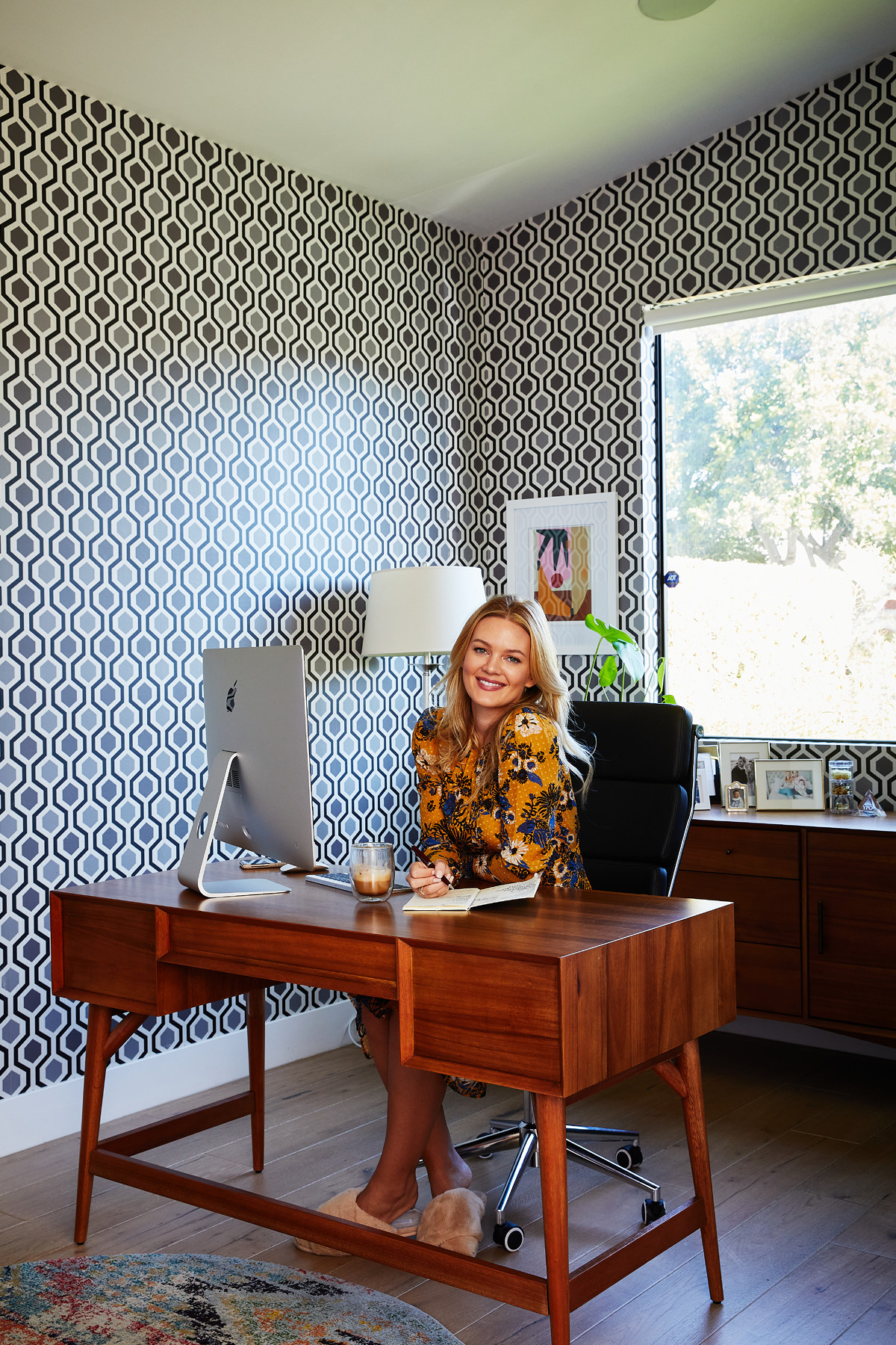 Kleinman stretched her design skills in this stylish home office with patterned wallpaper.West Elm Desk |Williams Sonoma Coffee Mug |Cole & Son Wallpaper |Pottery Barn Lamp.