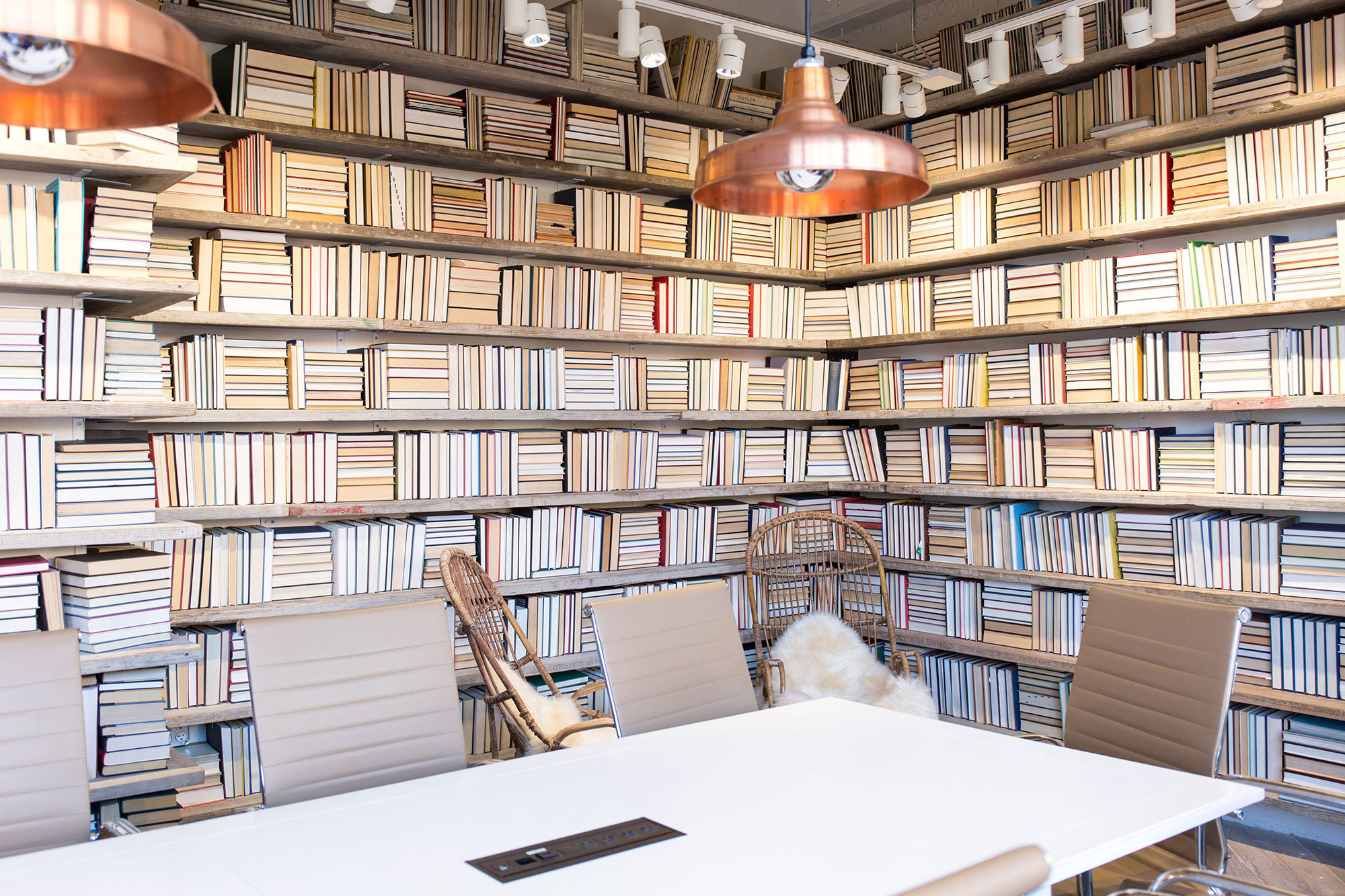 Three out of the four walls of Naficy's personal conference room is covered in old books from a public library, a design choice she credits Ermshar for imagining.