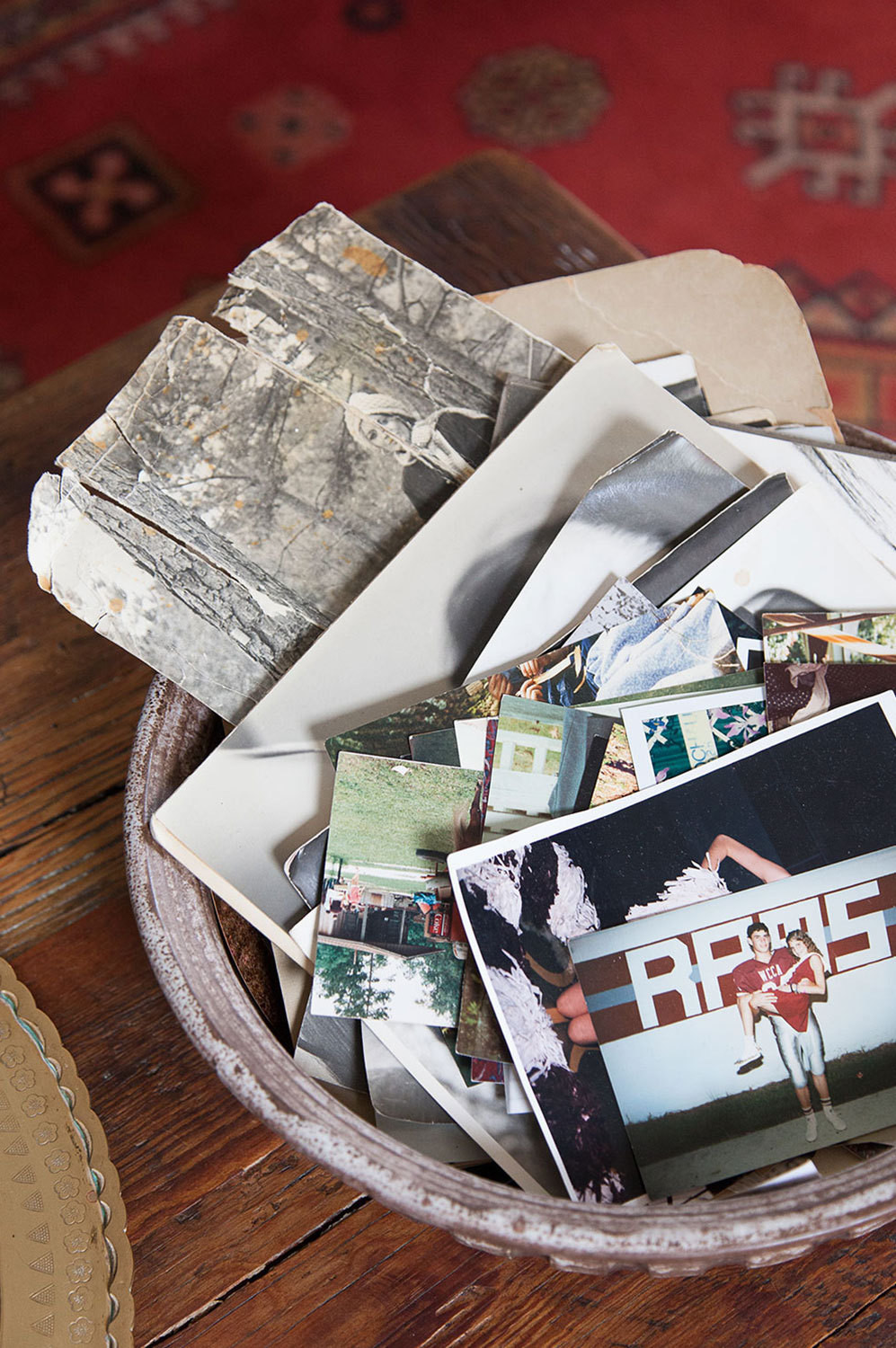 A bowl filled with sentimental photographs sits atop a coffee table Lindsey's father had made for her.