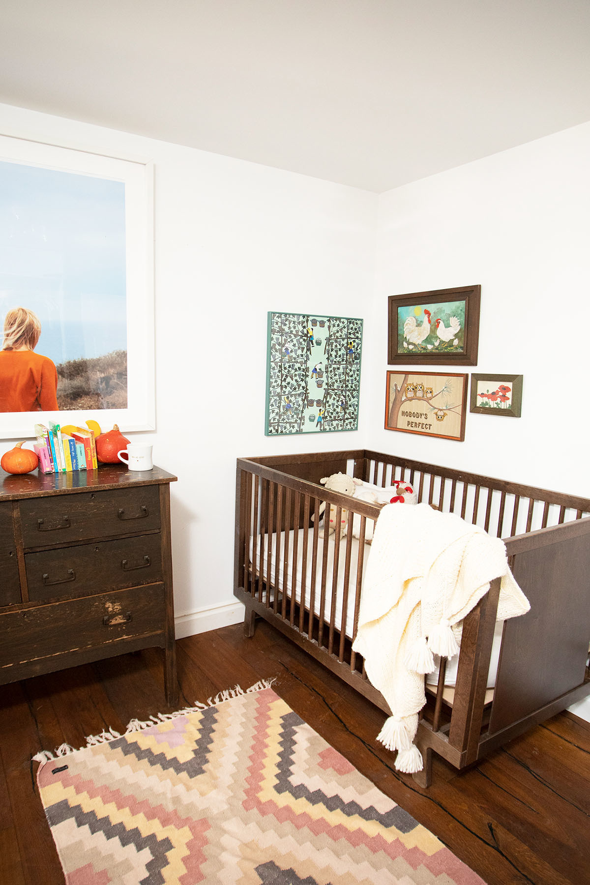 Sophie's nursery — located directly off the kitchen and complete with repurposed vintage furniture and oversized prints — evokes a relaxed aesthetic. Jimmy Marble Print | Vintage Dresser | Vintage Crib | Target Bedding | Target Throw | Vintage Runner | SFMoMa Store Assorted Accent Pieces | Vintage Toys.
