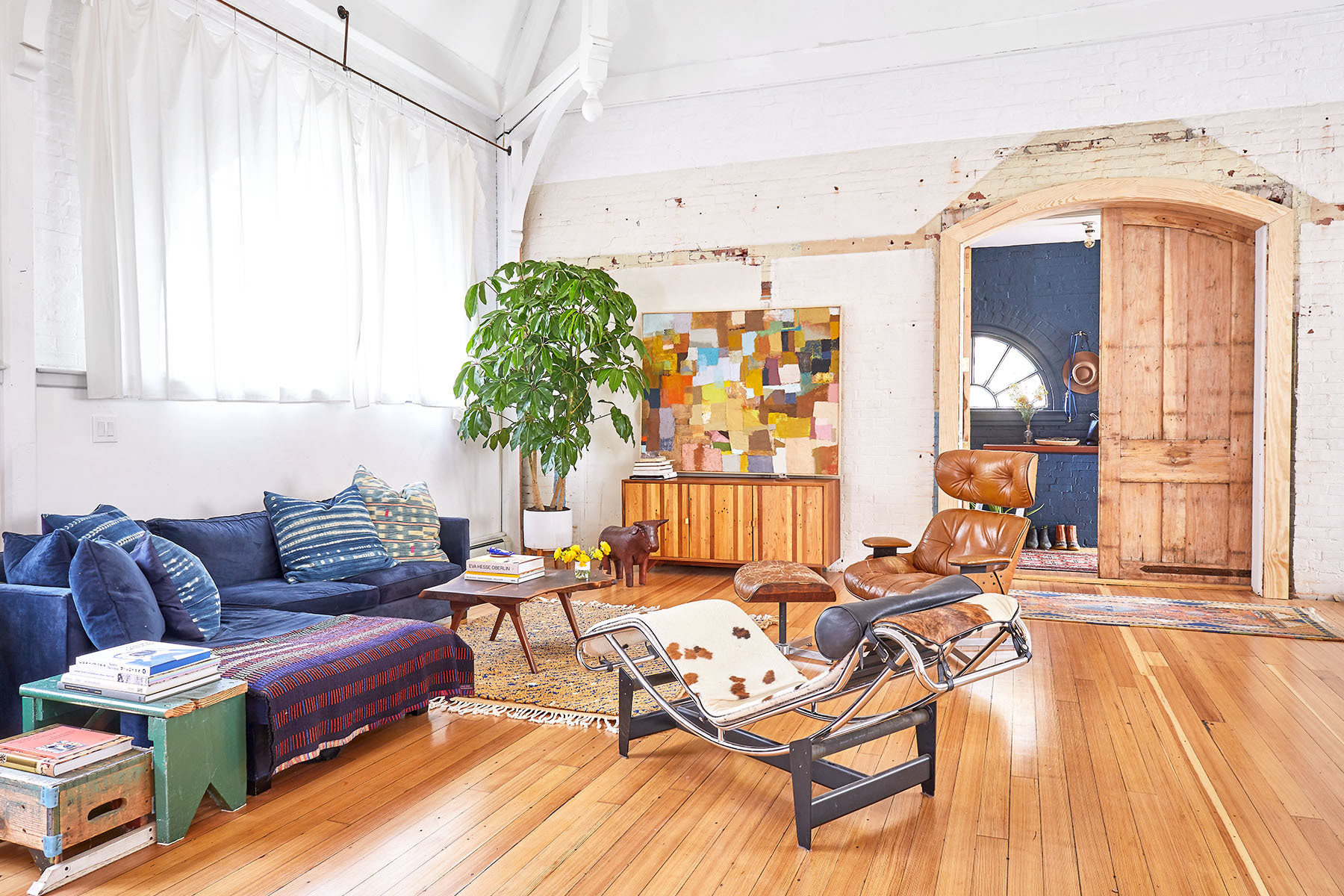An open living space, complete with a vintage blue sectional sofa and brown leather Eames lounge chair, gives the home a lived-in, layered appeal. Benjamin Moore Paint | Charlotte Perriand Chaise | Abercrombie & Fitch Vintage Ottoman | Vintage Sofa | Jungil Hong and Andrew Mau Rug | Jamison Sellers Buffet Table | Vintage Side Table | Farrow & Ball Paint.