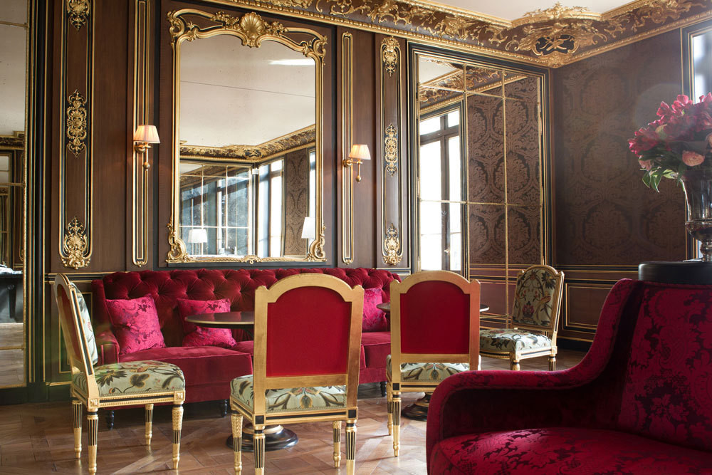 Gilded wall panels and upholstered seats embrace opulence in the hotel's private lounge.