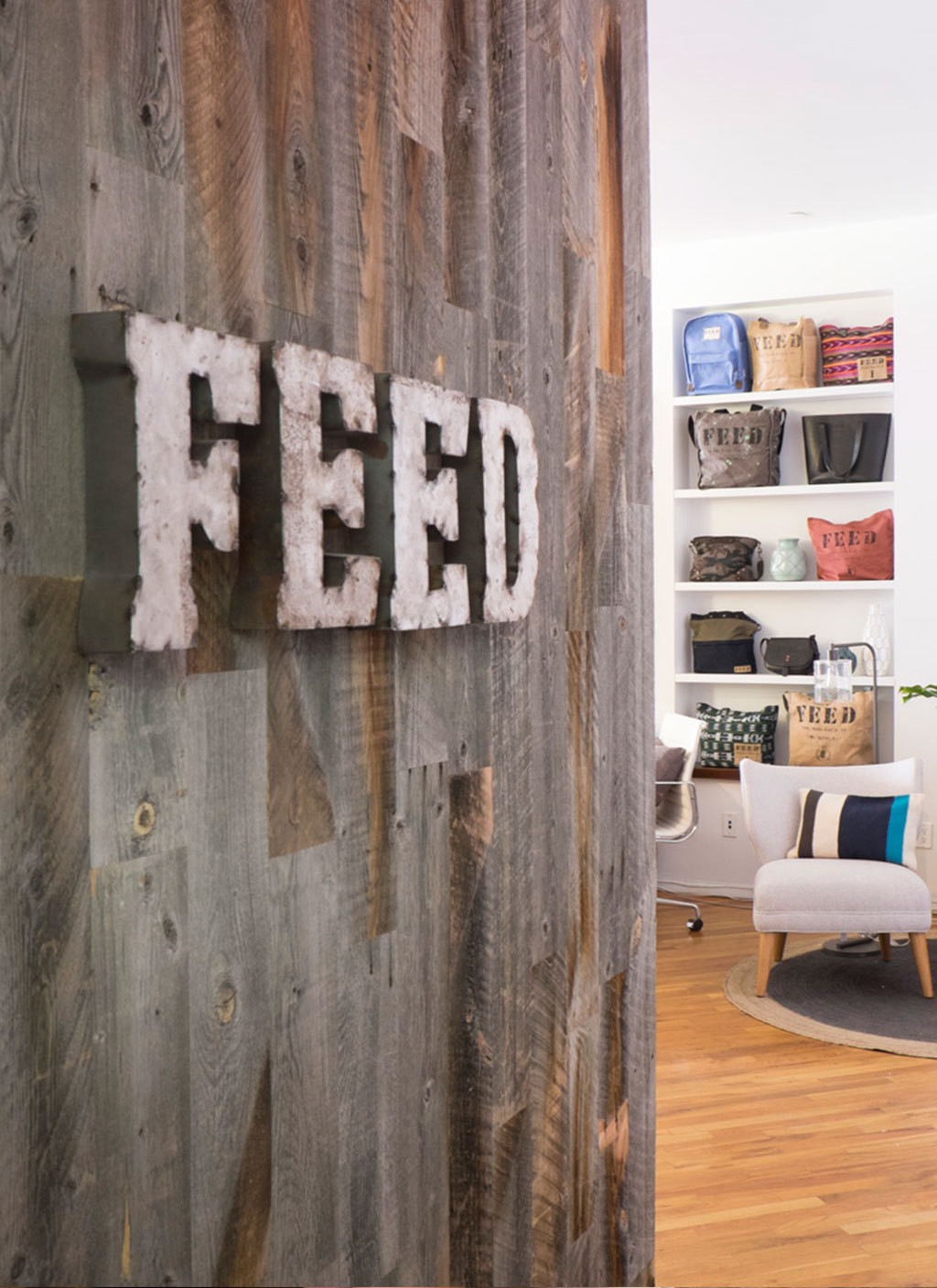 A reclaimed-wood wall bearing the organization's logo greets visitors to the office.