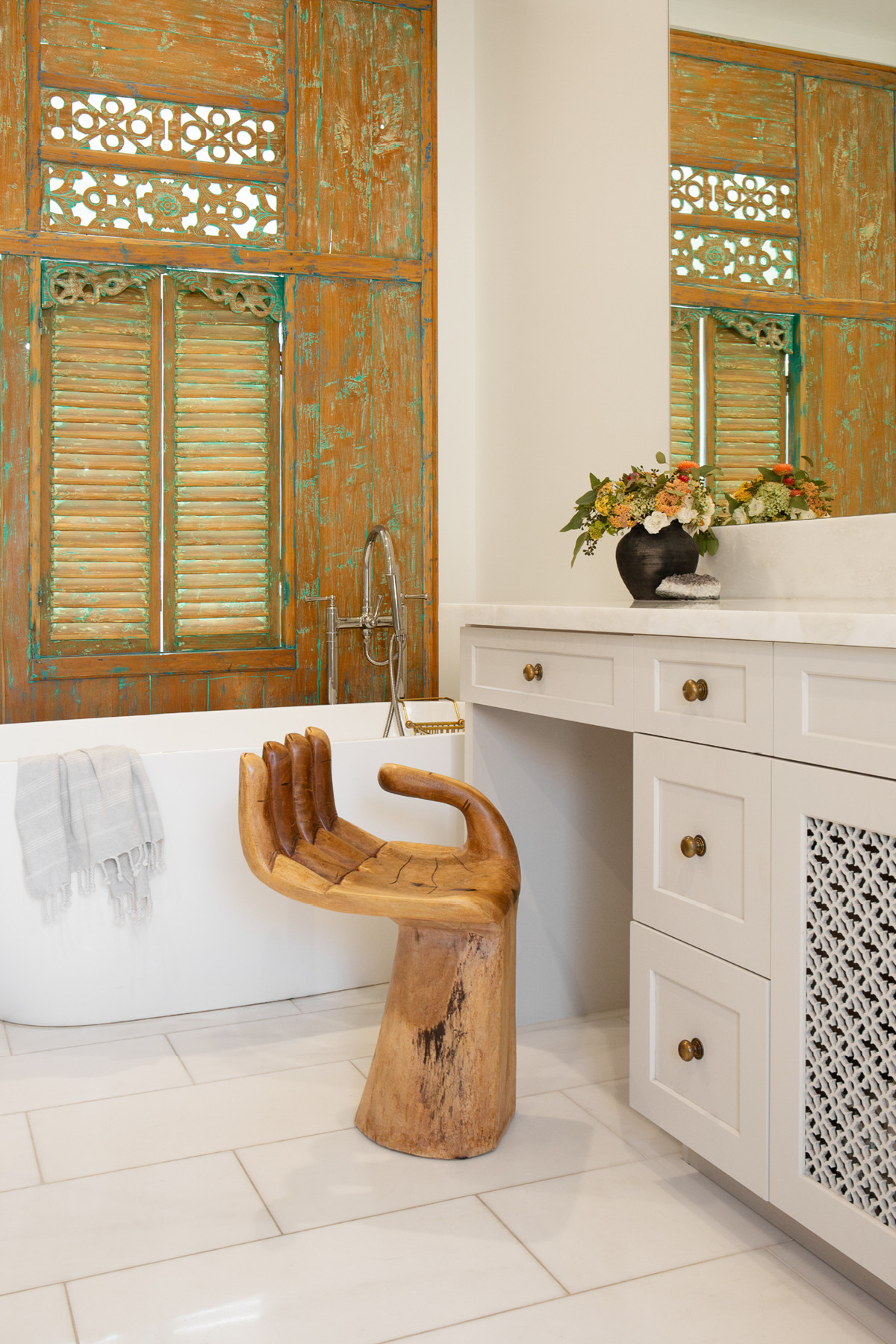 O'Brien's main bathroom strikes a happy medium between form and function, thanks to the wood-carved wall and Baliense hand stool. Vintage Hand Stool |The Home Depot Tub | Custom Cabinetry |Clé Tile Tiles.