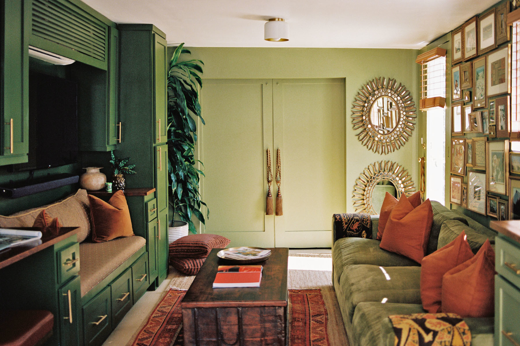 Stylist Courtney Madison's converted green pool house serves as a welcome retreat from the L.A. heat. Behr Paint | Behr Accent Wall | Total Design Furniture Custom Sofa | Vintage Rug | Craigslist Coffee Table | Vintage Mirror | Custom Bench Seat | Goodwill Vintage Door Hangers | Repurposed Cabinetry | CB2 Hardware | CB2 Throw Pillows.