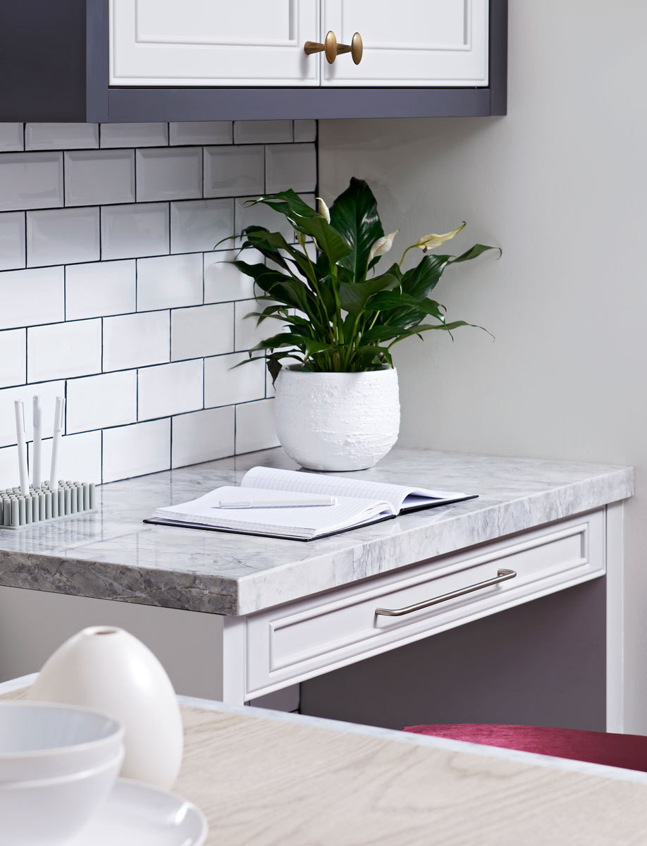 Topped with a marble-like porcelain, a petite workstation makes maximum use of a tight space in the kitchen.