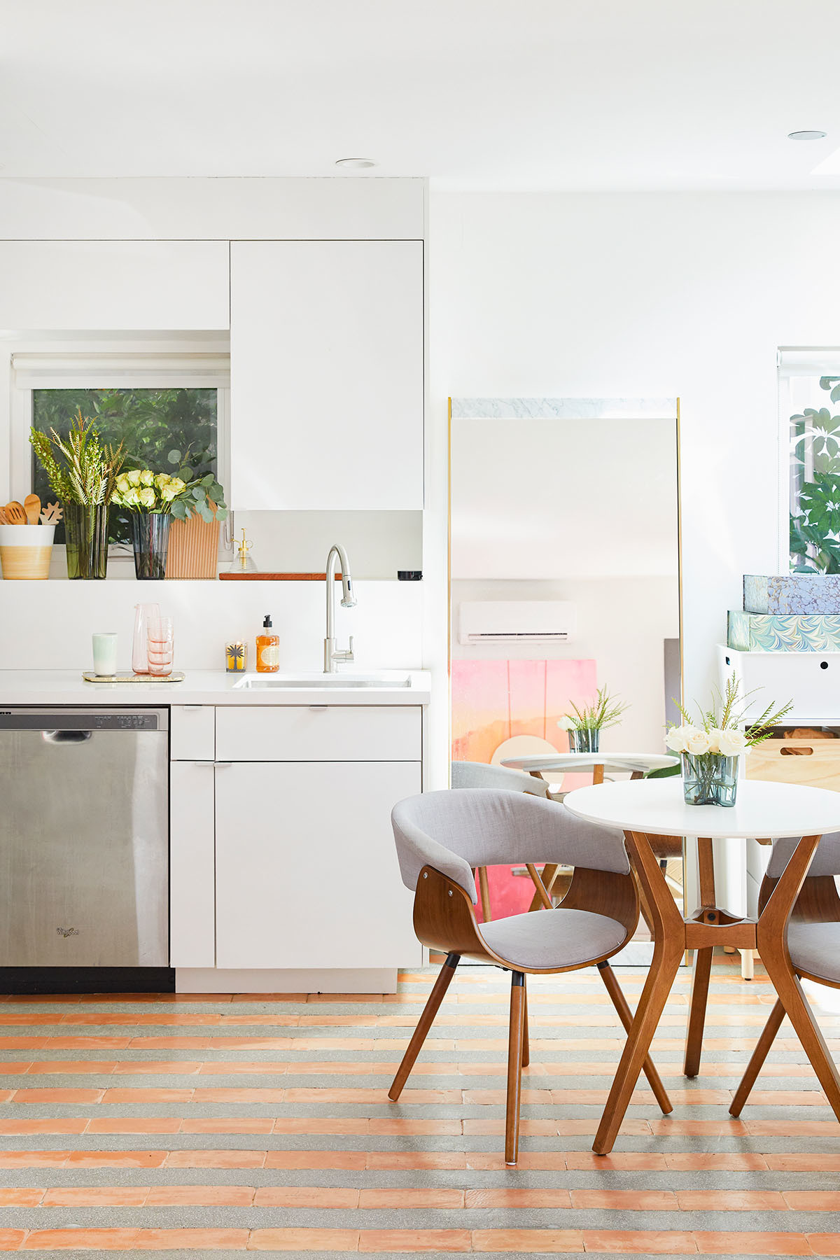 The couple opt for Danish-inspired furniture, and a smaller breakfast nook over a full-scale dining table. Vintage Dining Table | Vintage Dining Chairs | IKEA Shelves | Amana, Whirlpool Appliances | Alvar Aalto for Iittala Vase.