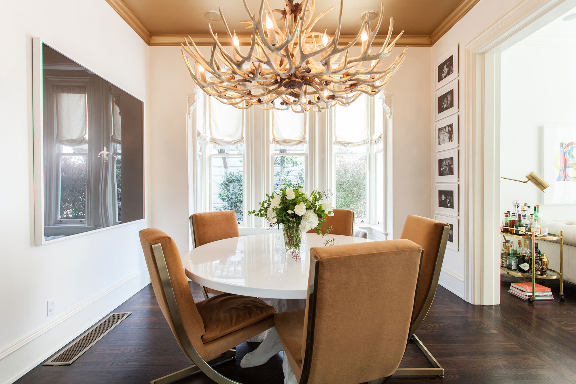 An antler chandelier lends an organic touch in the sleekdining room of a San Francisco home owned by Jessica and Matt Farron and designed by Leanne Ford.