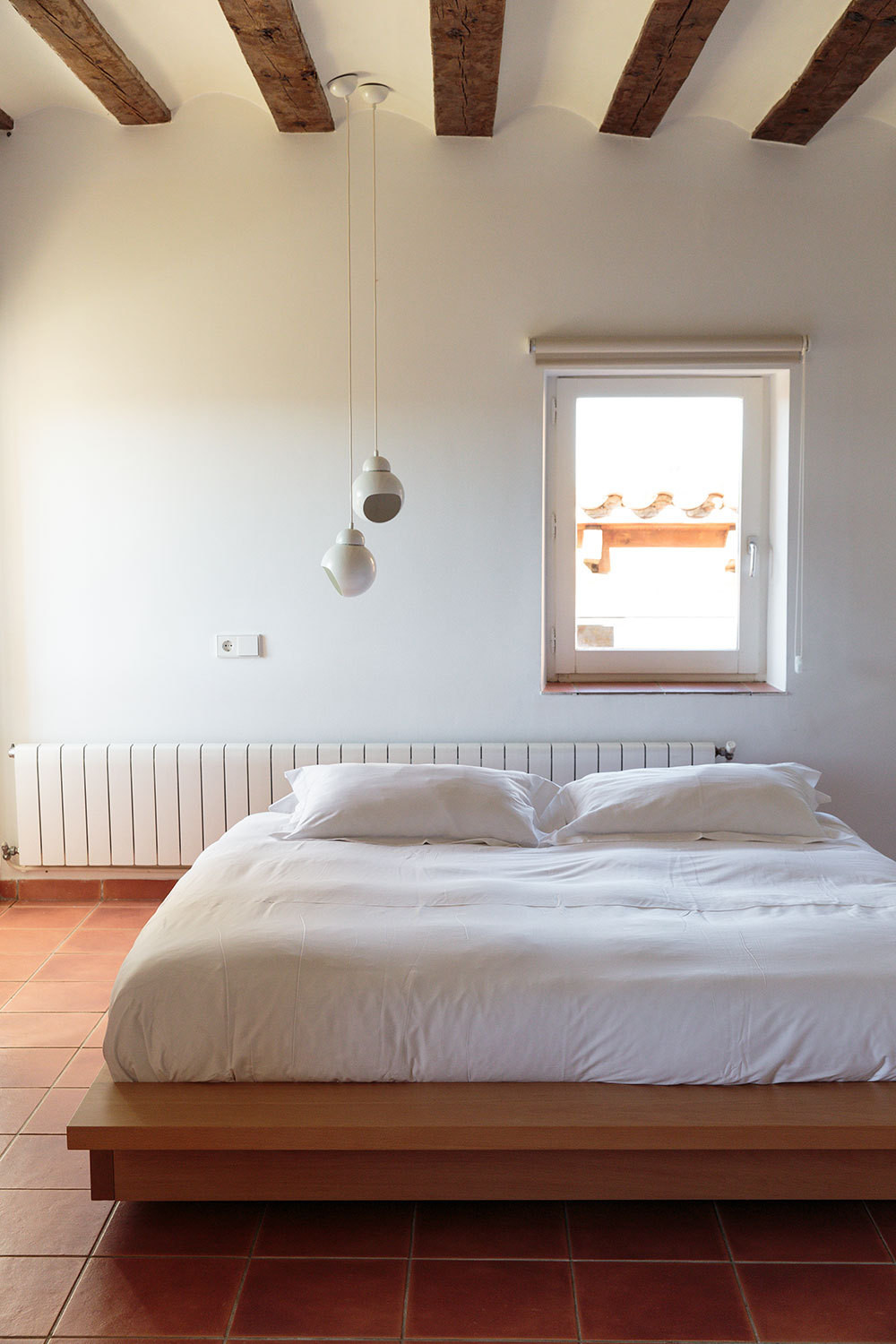 Alvar Aalto lighting above a platform bed in the Nordic guest room.