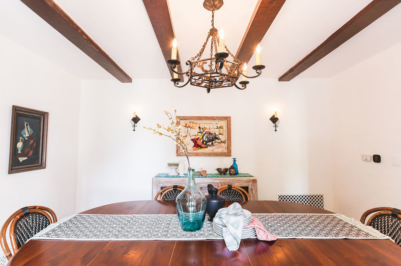 In the dining room, original wood beams helped to guide the tonal palette of natural woods and emerald tones in the accessories. The vintage chandelier presides over the table that the family has owned for decades and classic French bistro chairs from Maison Midi.