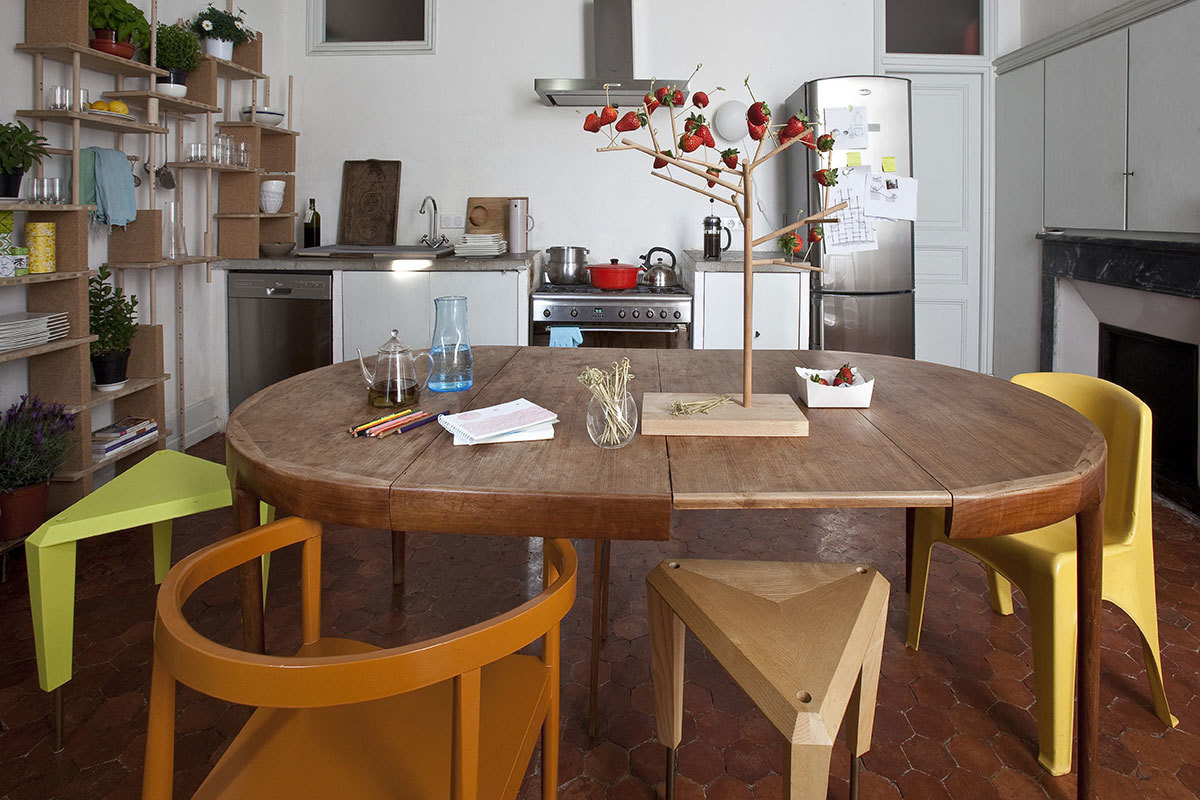 The kitchen is home to an extendable dining table in oak. An eclectic mix of seating accompanies the table, including a vintage yellow chair and 'Ziggurat' stools by Smarin. Atop, a piece called 'Mangier, Eating Tree' by Smarin.