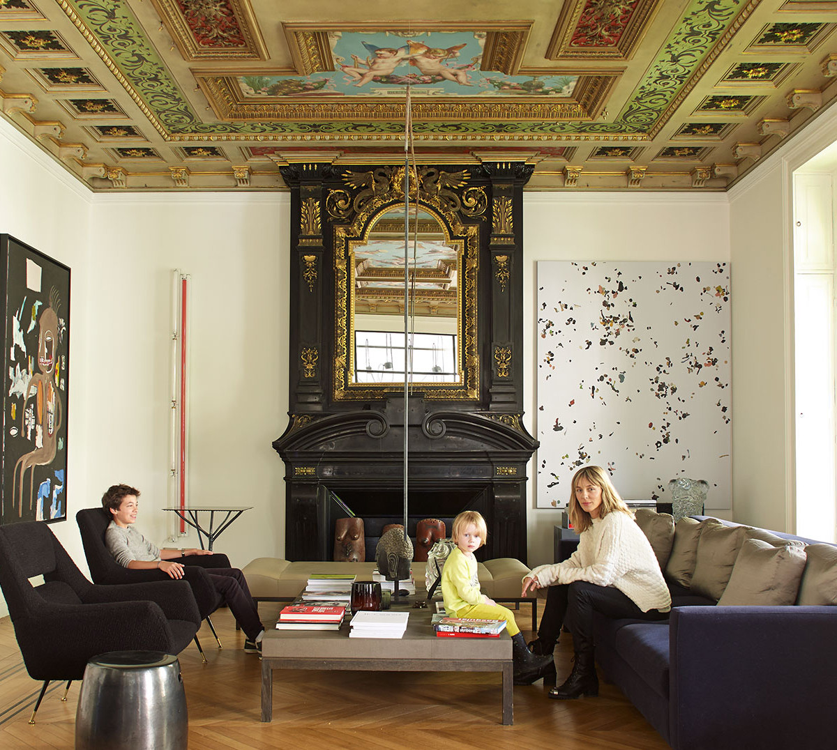 Cécilia Bönström and two of her children, Victor (far left) and Emil-Milo, in their Paris living room, surrounded by works of artists including Jean-Michel Basquiat, Dan Flavin, Adam McEwen, and Katinka Bock.