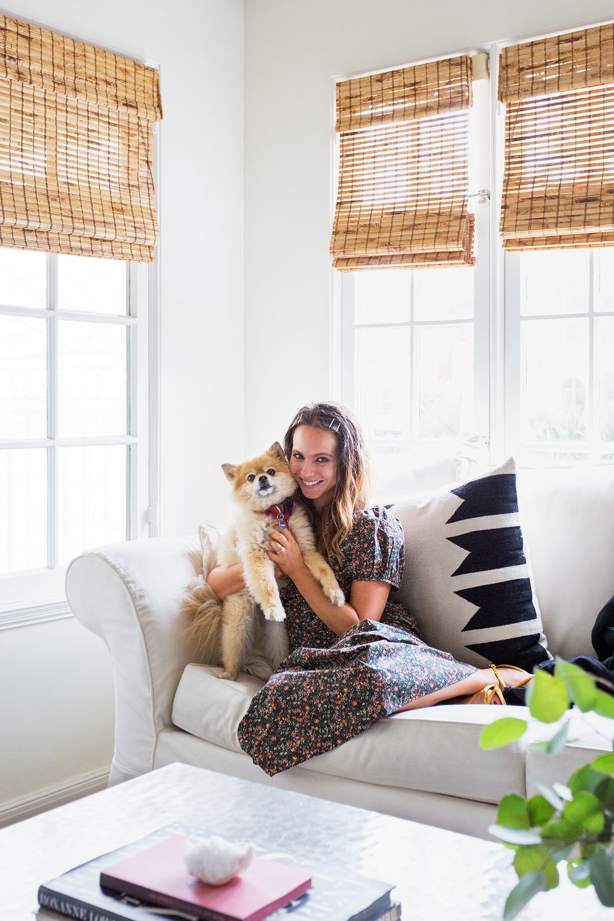 Margolis, pictured with pup Bear, believes more renters should consider investing into the look and feel of their homes. Pottery Barn Sofa | The Citizenry Pillow | Kathy Kuo Coffee Table.