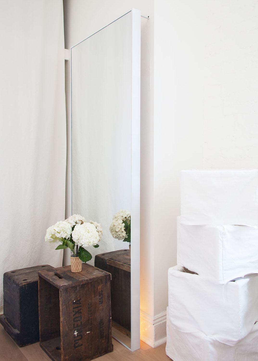 An oversize mirror and fabric-covered storage boxes preserve the spa-like mood.
