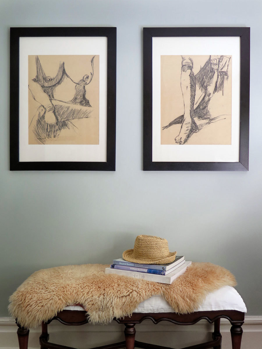 A vintage bench and a pair of sketches belonging to the homeowners make an artful vignette in the master bedroom.