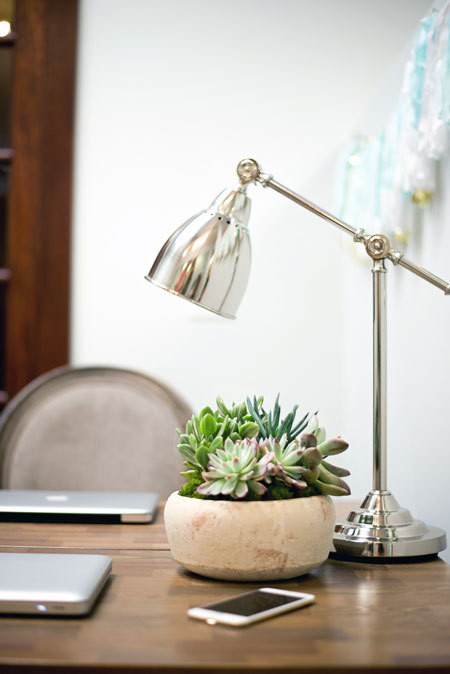 A swing-arm desk lamp illuminates the shared desk area above a succulent planter. Threshold Mixed Material Desk, Target.