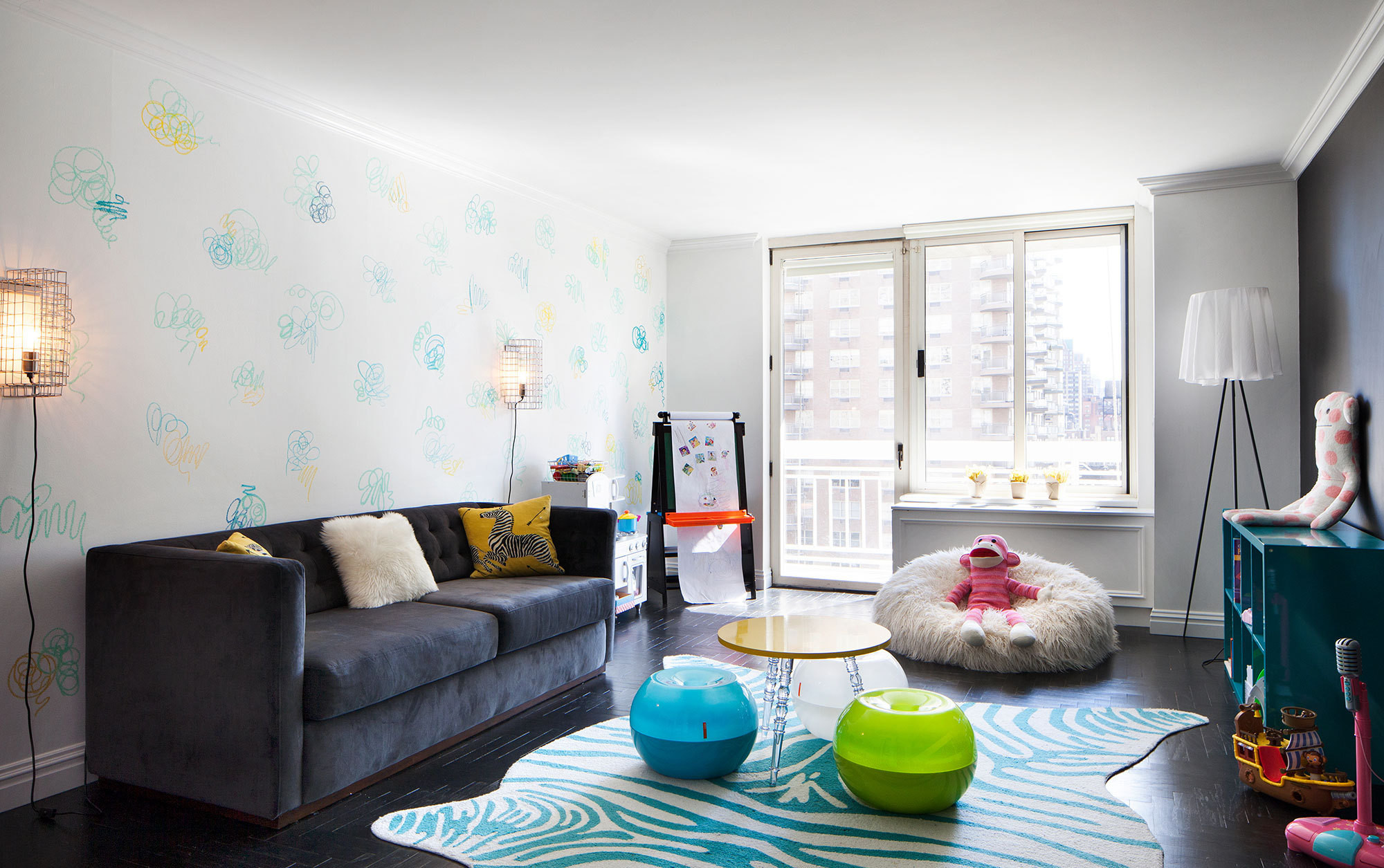 A teal, zebra print rug anchors the dark floors of the play space, which also features cage wall sconces from CB2 and a furry bean bag.