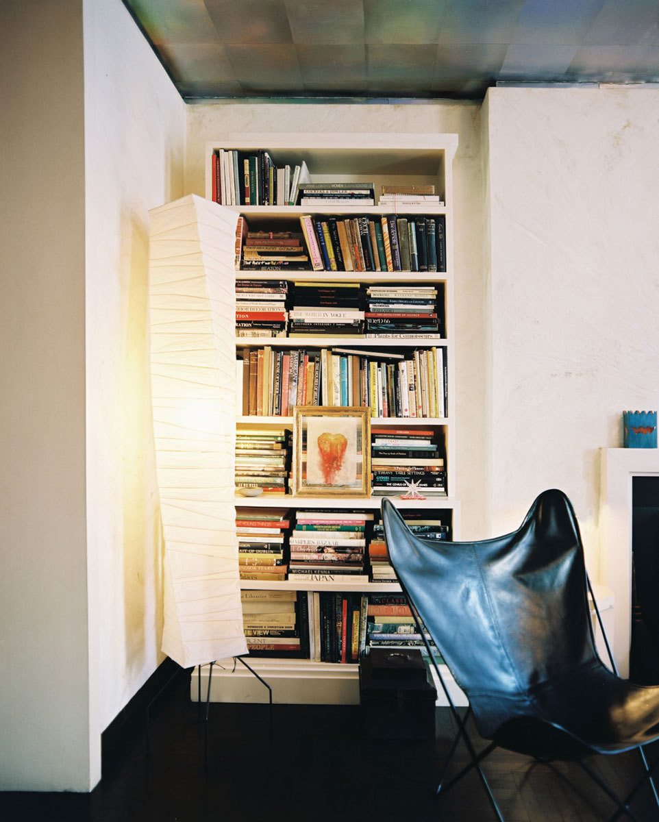 A leather butterfly chair stands before a full bookshelf.