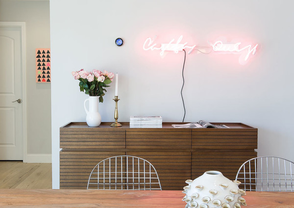 We love the neon sign in the place. What does it say and who is it by?
