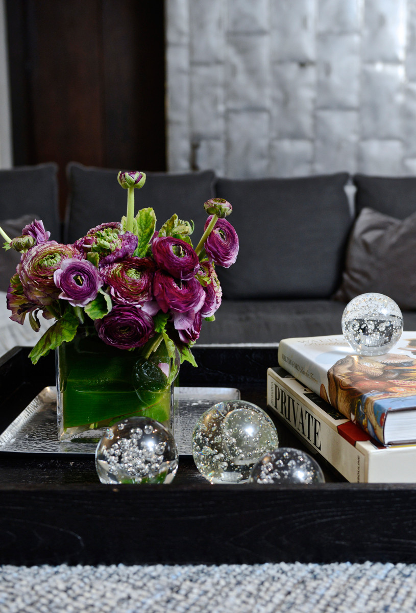 An arrangement of fresh flowers and glass objets keep the space feeling light and airy.