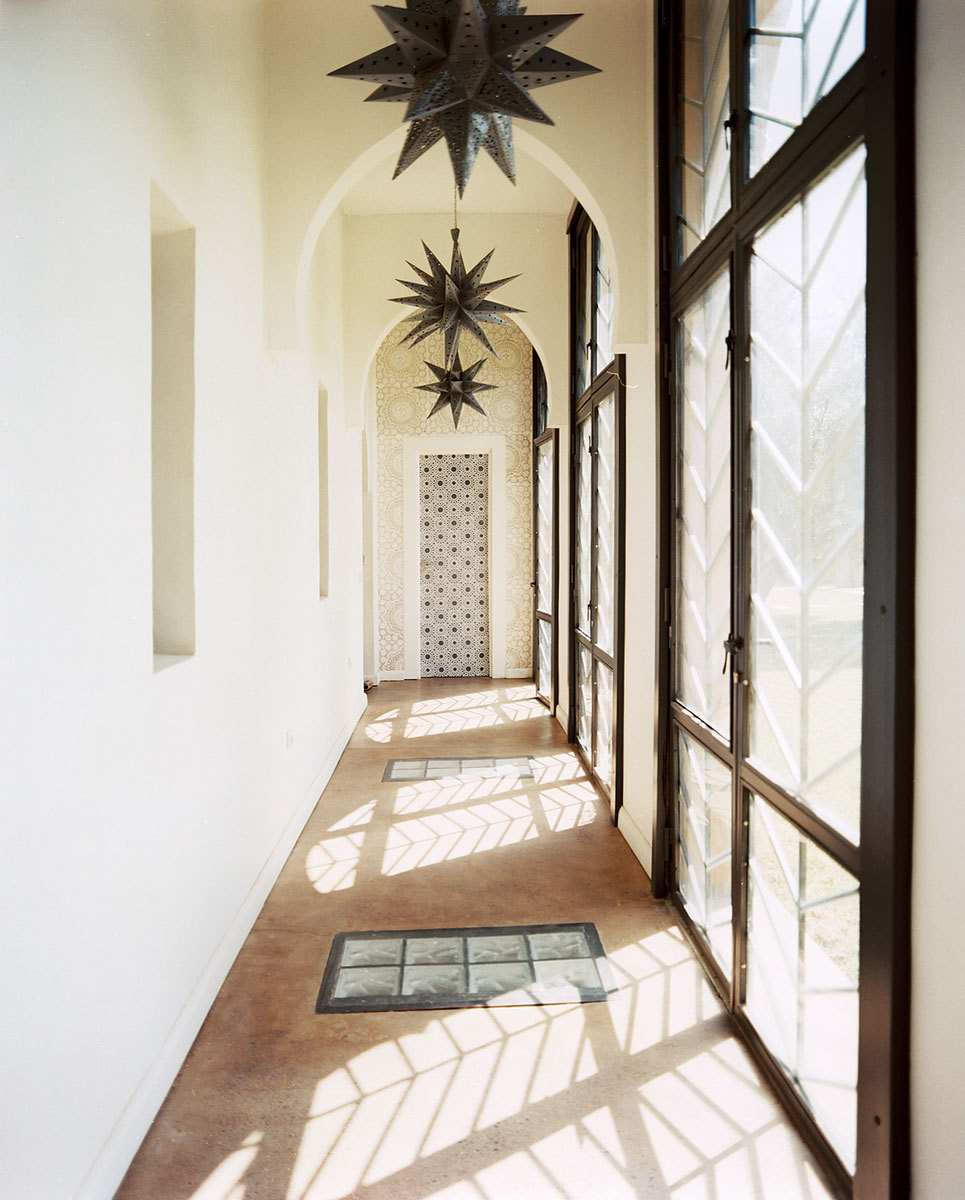 Star-shaped lanterens, with their delicate filagree, line a glass-enclosed hallway overlooking the swimming pool.