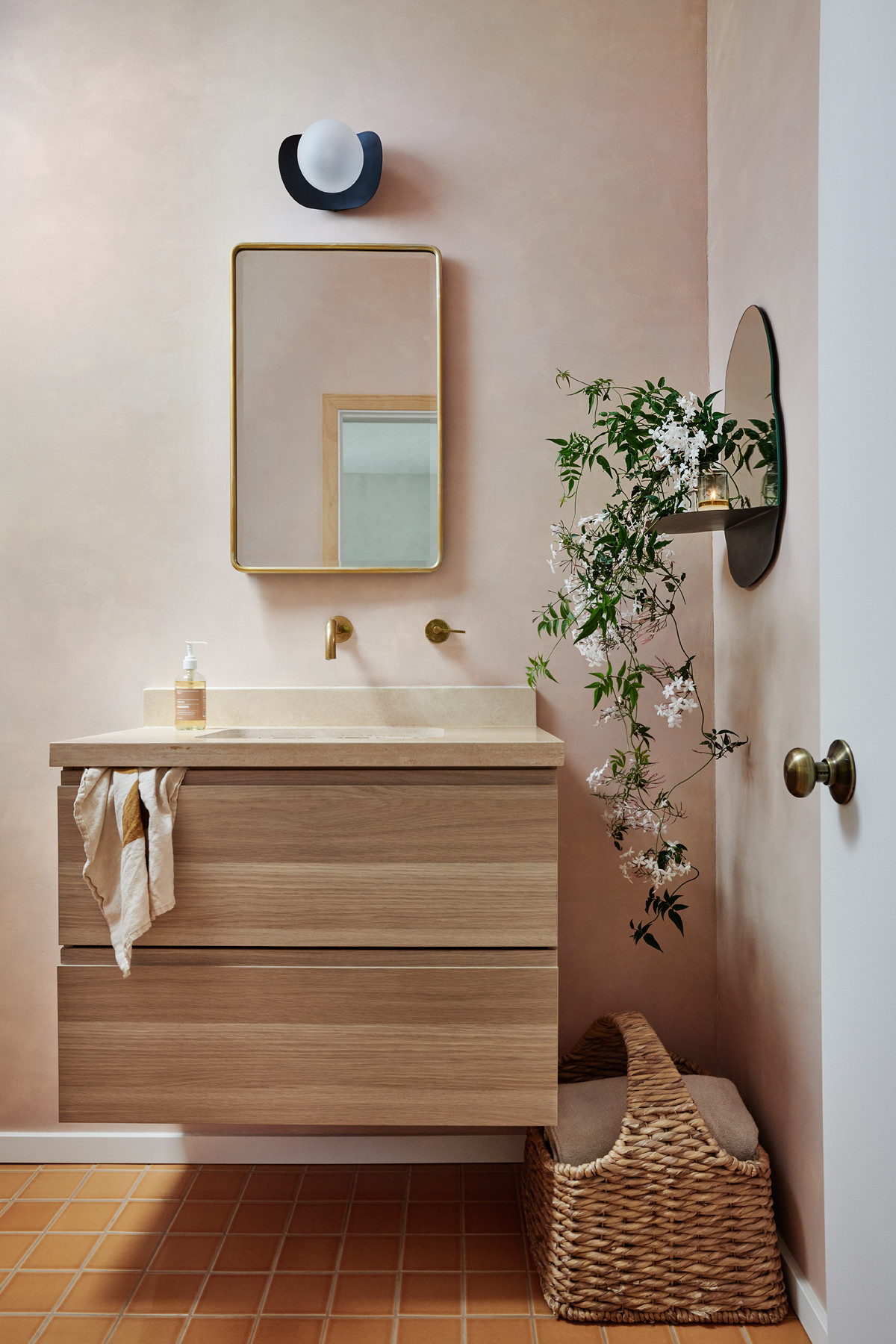 A peachy paint treatment in the main bathroom complements the tile. Jasmine from del Rio's garden is perched atop an Amara mirror. AmaraMirror;Pottery Barn Mirror; Fireclay Tile;Portola Paints.