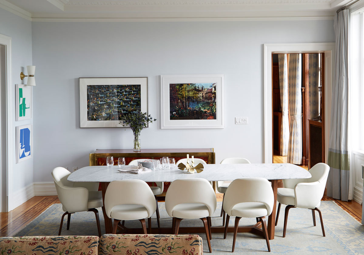 Midcentury-style Saarinen for Knoll armchairs and a marble-topped Poliform table complete the scene in adining room designed by Fawn Galli.