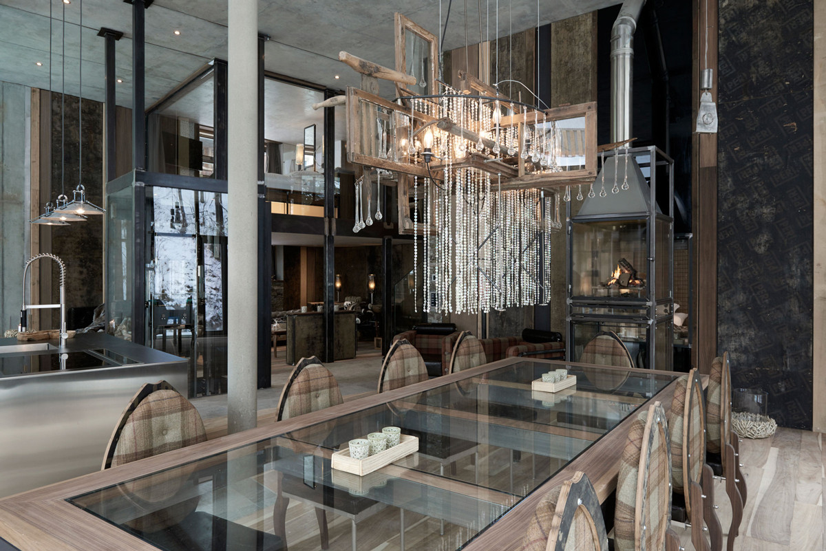 At the Luxury Loft, Heinz Julen's most recent project, a chandelier composed of rustic window frames and a cascade of crystal hangs over a glass table framed in walnut, which can be hoisted out of the way to free up space for entertaining.