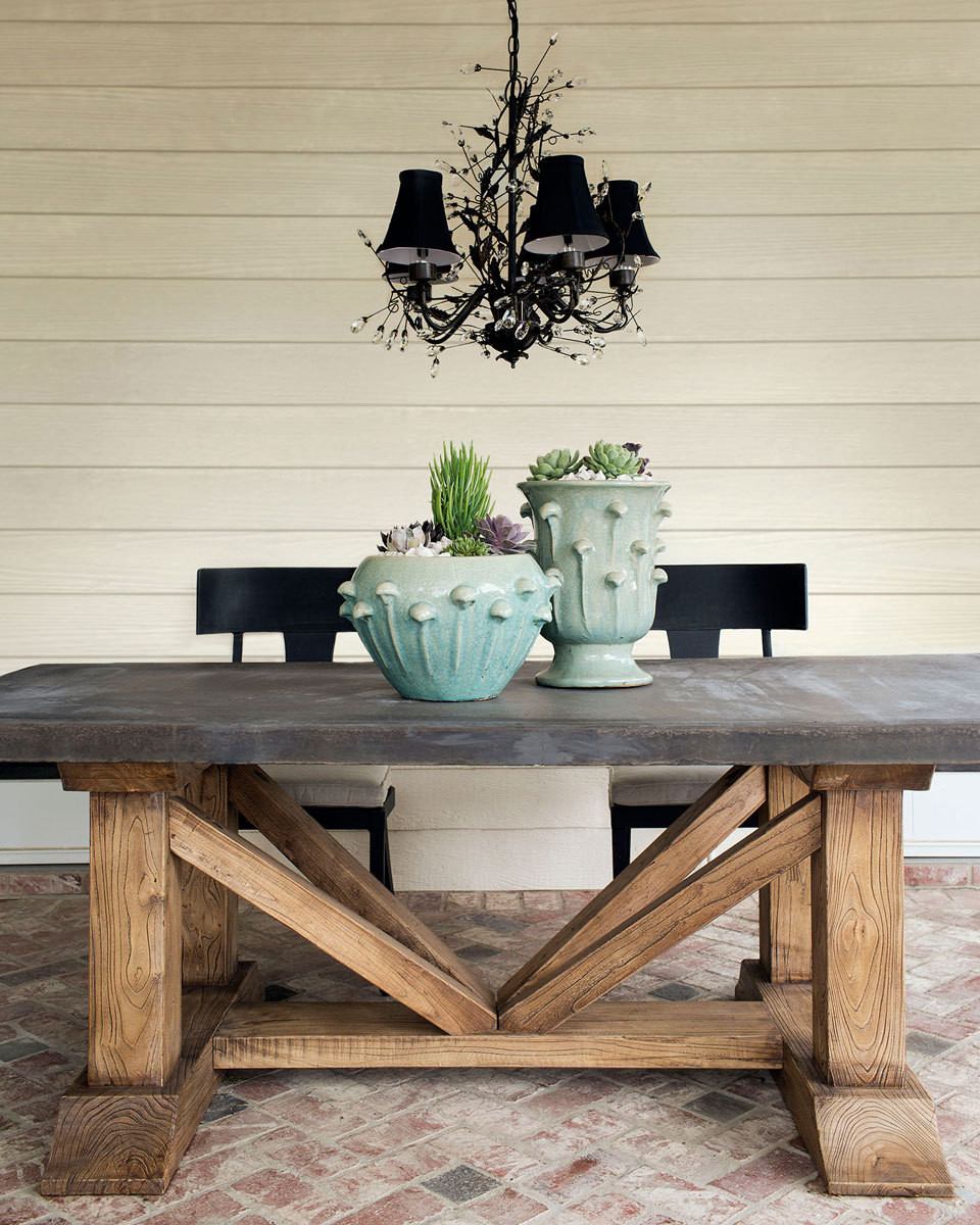 An outdoor table of reclaimed elm topped with reconstructed stone is paired with Palisade Dining Chairs and a fanciful light fixture.
